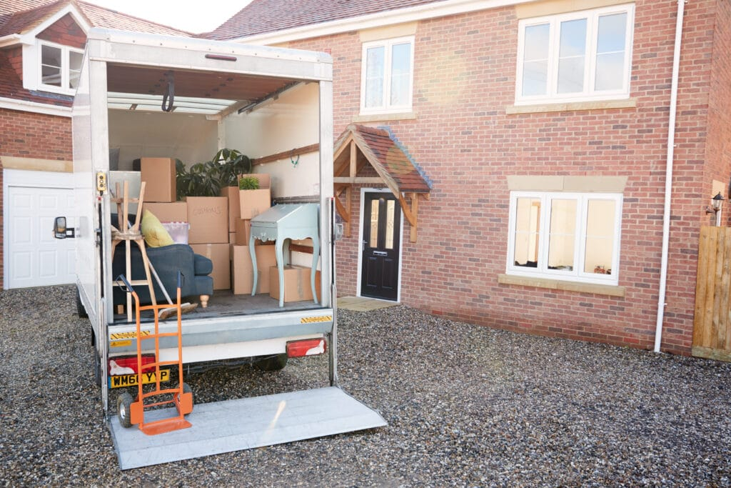 Removal Truck Waiting To Be Unloaded Outside New Home On Moving Day